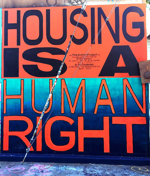 "mural in orange and blue that states ""Housing is a human right,"" in partnership with the Gubbio Project"