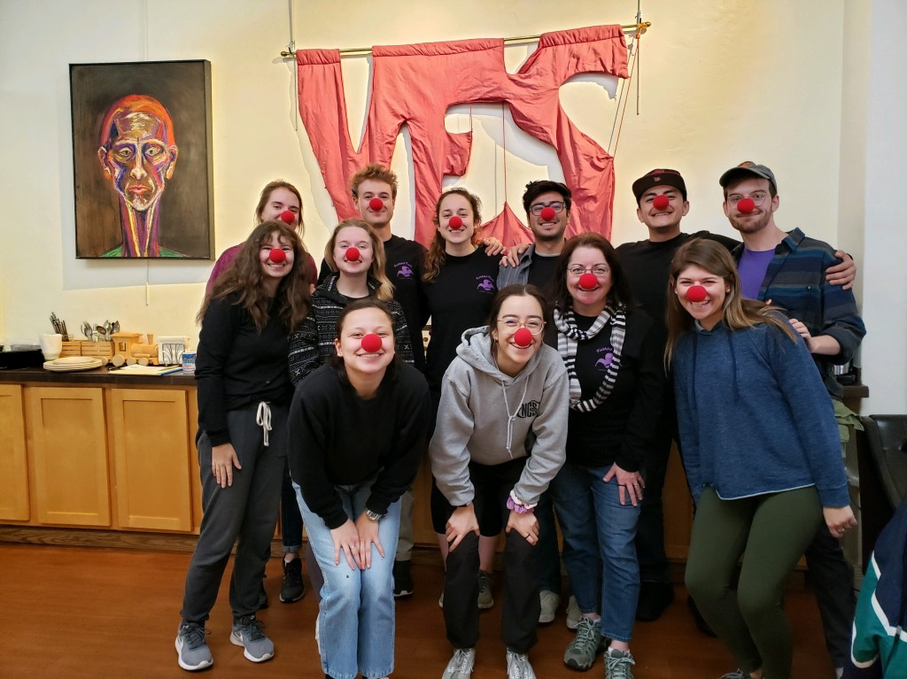 the red clown noses the group wears & the large yes hanging behind them are iconic aspects of the Faithful Fools